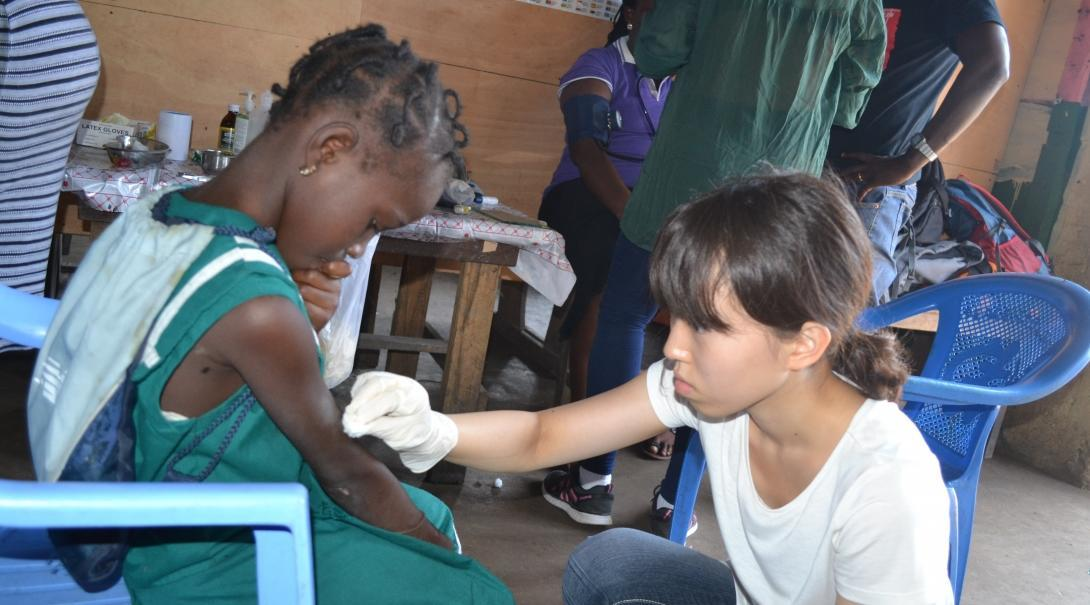 An intern gains medical work experience cleaning a wound on our project for teenagers in Ghana